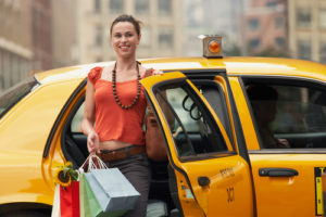Woman Stepping Out of Taxi Cab with Shopping Bags