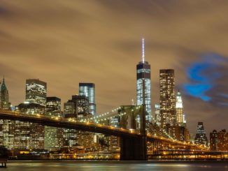 The Brooklyn rie with the famous NYC skyline illuminated in the background