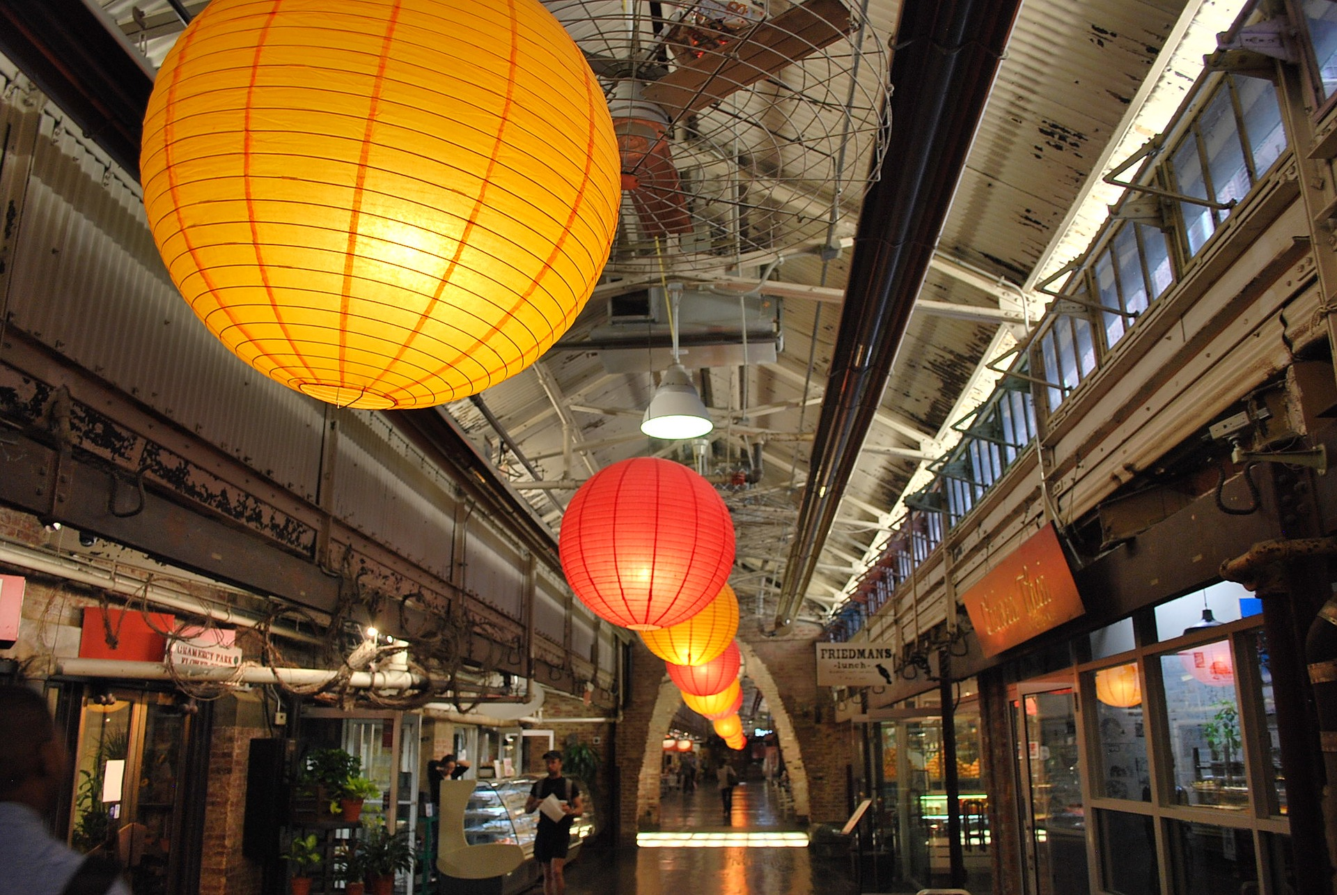 Lanteerns light up the chelsea market in New York City as customer buys food in background