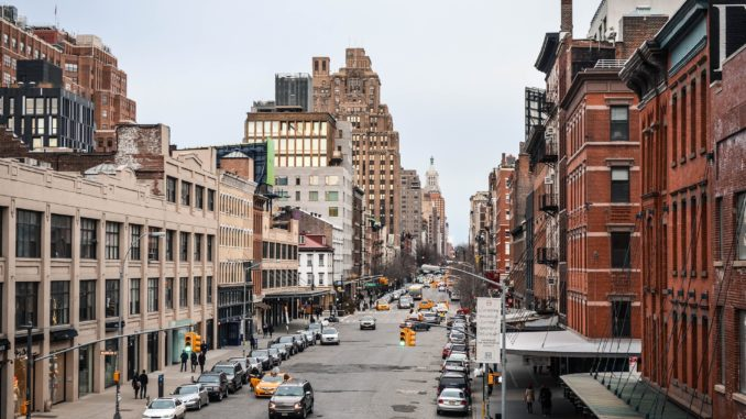 Padestrians and cars head up the street in the meatpacking district NYC