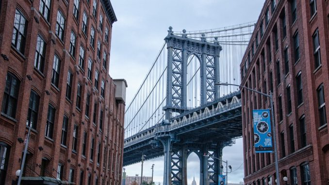 The Brooklyn Bridge between two rows of buildings in DUMBO, New York