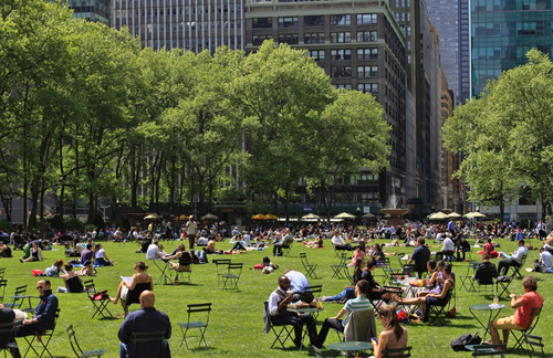 People sitting on chairs and enjoying a nice day in Bryant Park in New York City