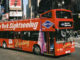 new york sightseeing bus drives past pedestrians in Times Square