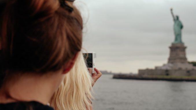 A view from the ferry of tourists taking pictures of the Statue of Liberty.