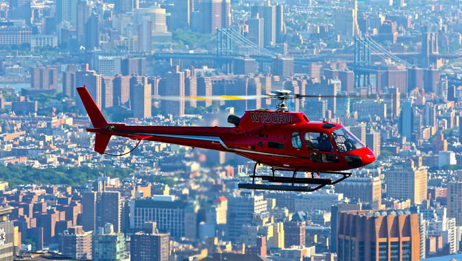 Red helicopter hovers high above NYC's buildings