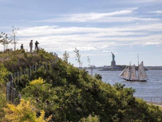 View of the Statue of Liberty from Governors Island as sail boat passes, in New York Harbour