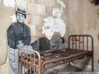 French Artist, JR, depicts blown up photos of immigrants on the wall in front of an old-fashioned bed in the Ellis Island Hospital