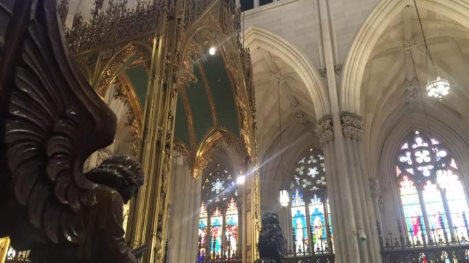 Sun shines through colourful glass into St. Patrick's Cathedral in Midtown Manhattan, New York City.