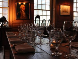 Empty glasses sit on wooden table in front of a portrait, at New York City's Fraunces Tavern