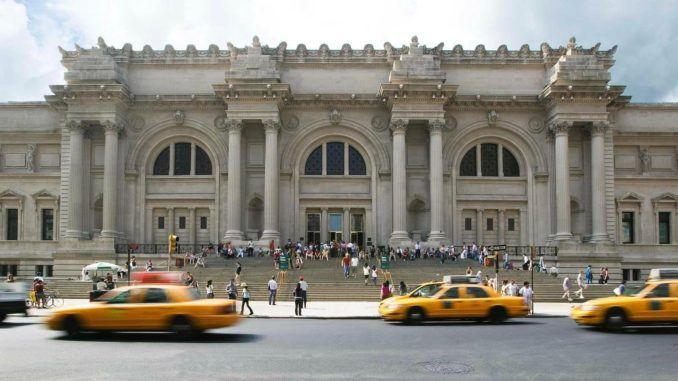 Yellow taxis fly past people queuing outside the Metropolitan Museum of Art located on Fifth Avenue, New York