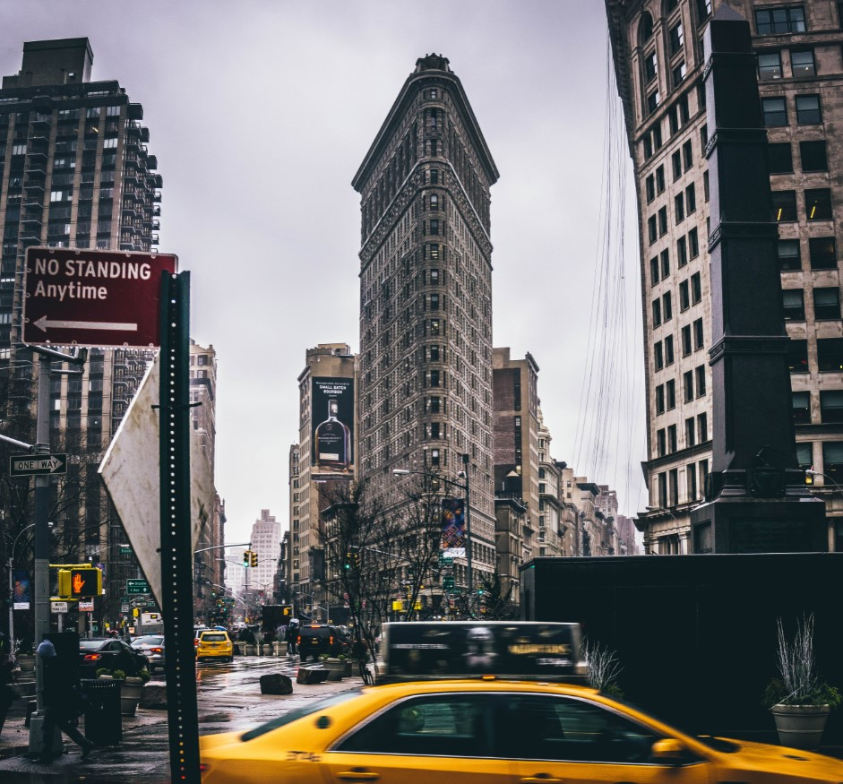 Taxis pass one of New York City's most unique structures, the Flatiron Building.