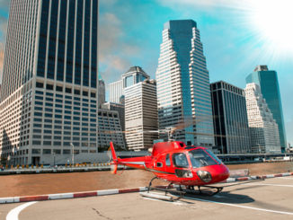 Red helicopter ready to take off in New York summer skyline.