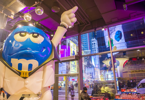 Inside M and M world new york as model points to ceiling