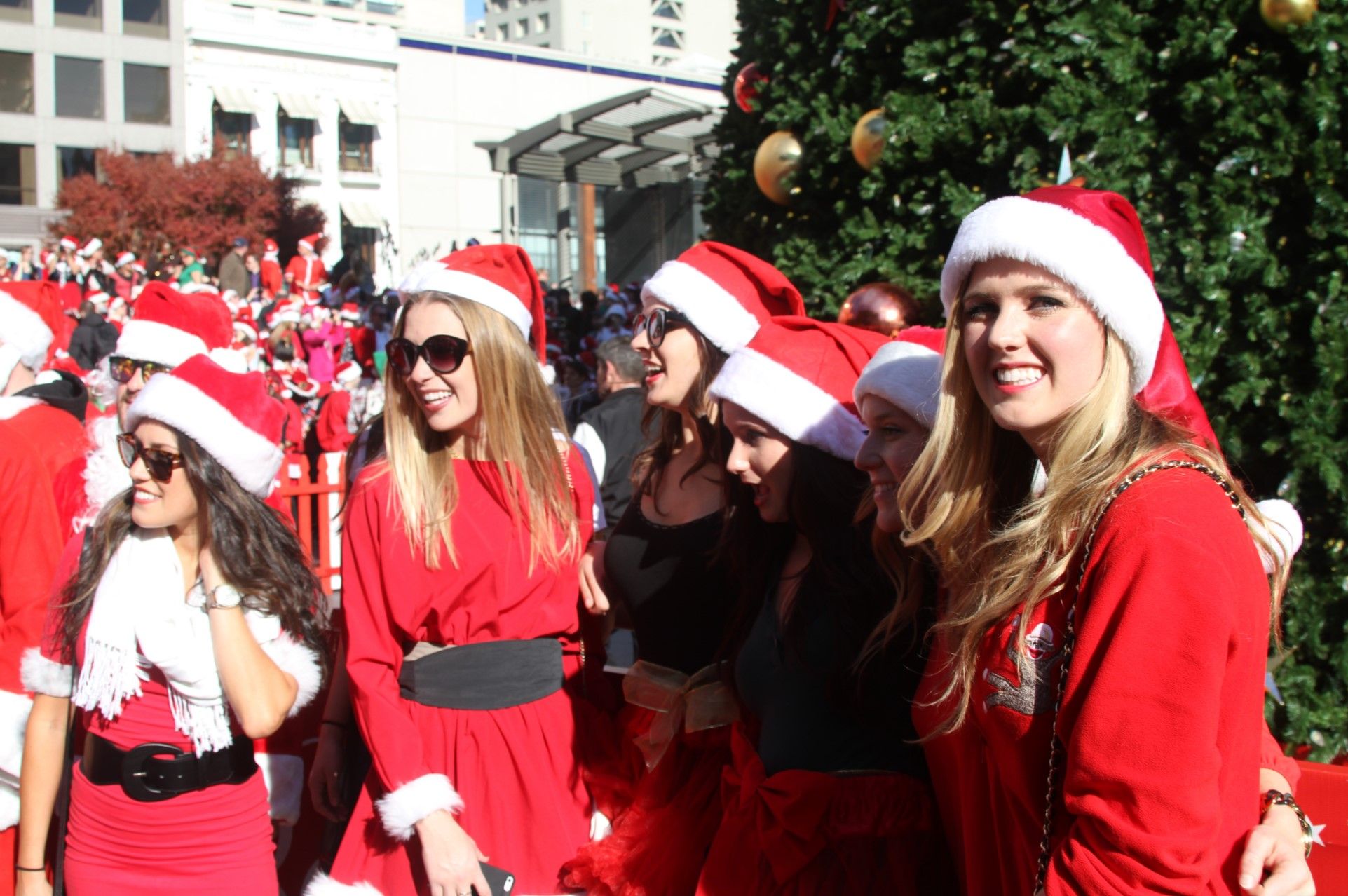 attractive females dressed as santa claus pose for picture