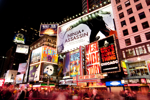 Night scene of Broadway at Times Square in Manhattan (New York City) with all the lit up billboards and advertisements, and many tourists people walking by.