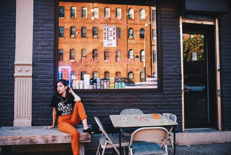 fashionable girl sits outside a pop up shop in the Bronx - new york in december