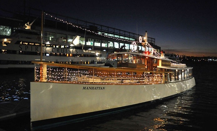 ship sits on pier with orange lights on board