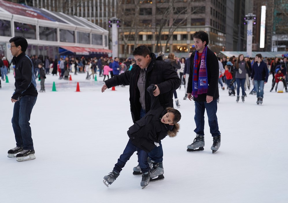 amilies skate on the ice at the Bryant Park ice rink