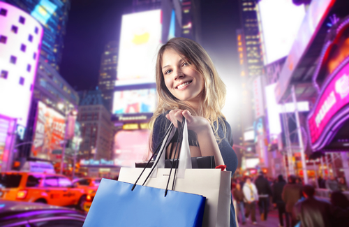 Woman with shopping bags with city shopping lights in the background