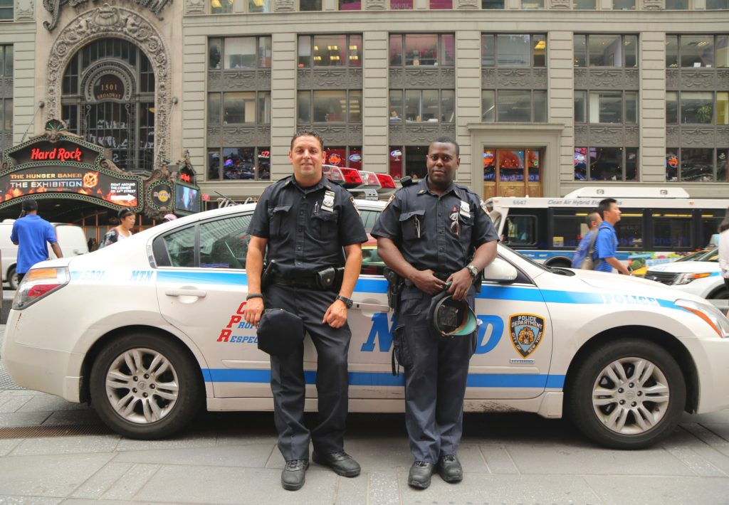 2 police officers stand in front of their vehicle in times square