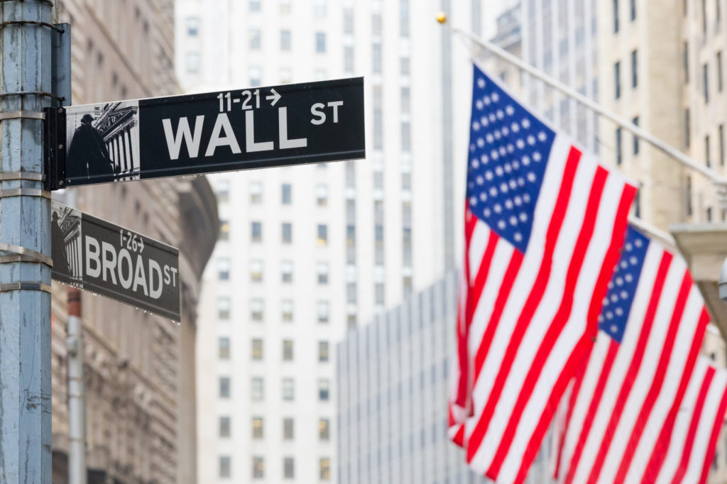 The famous wall street sign flanked by the flag of USA where to stay in new york