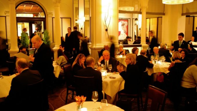 A busy Daniel Restaurant, Manhattan with guests busy chatting and sitting wine