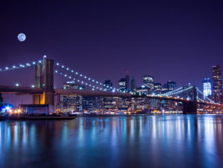 New York City's Brooklyn Bridge, at night, under a full moon