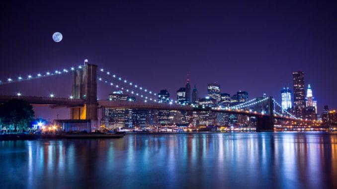New York City's Brooklyn Bridge, at night, under a full moon