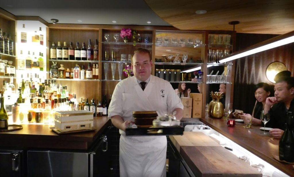 waiter with food ready to serve diners at the uchu sushi bar