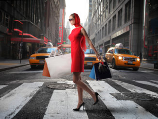 lady walking past yellow cabs with shopping bags - cheap shopping in new york