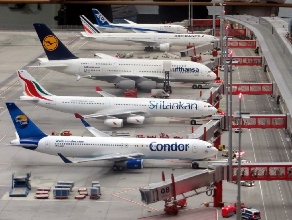 row of planes stands outside of airport