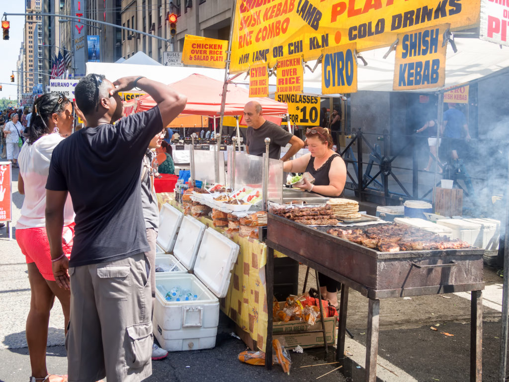 Street kiosk selling ethnic food at a street fair next to the Rockefeller Center in Manhattan - unique things to do in NYC