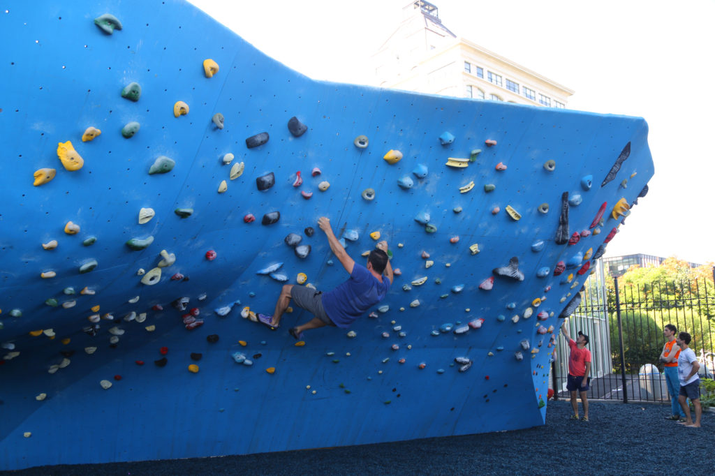 Rock climbing enthusiast scales the wall at Dumbo Boulders - unique things to do in NYC