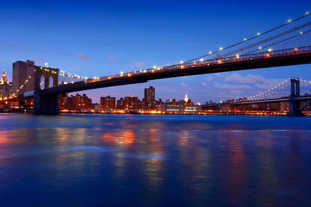 the illuminated Brookly Bridge over hudson river new york dinner cruises