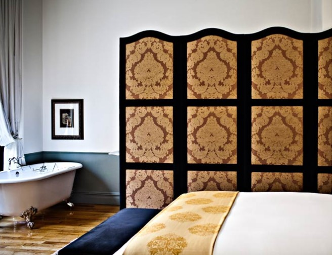 A bedroom in the NoMad Hotel features bed and a freestanding bathtub with a divider for privacy