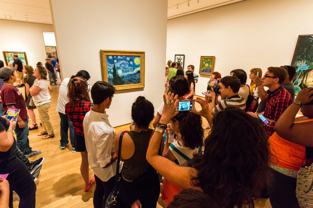 people gather around the work of Vincent Van Gogh at the MoMA in New York