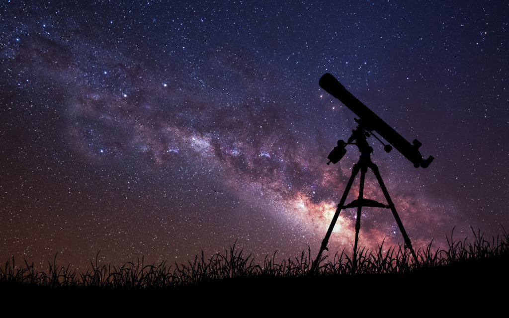 telescope points into the sky on a clear night