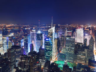 areal shot of Manhattan by night with all the major attractions illuminated