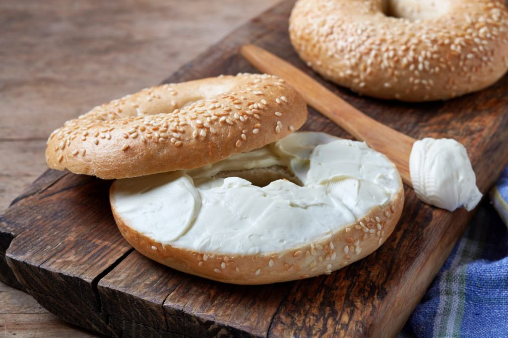 generous helping of cream cheese on a sesame bagel - things to eat in new york