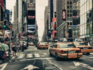 busy street in new york where people wait for traffic in front of yellow cabs - things to eat in new york